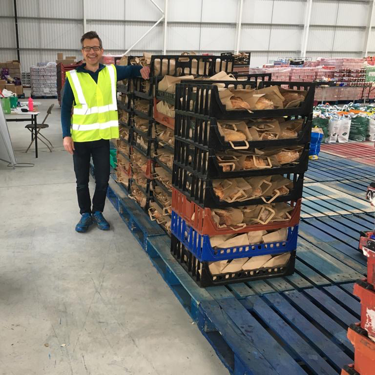 A photo of one of the worker at the Leeds City Council emergency food packages drop off stood next to several crates of Leeds Bread Co-op loaves
