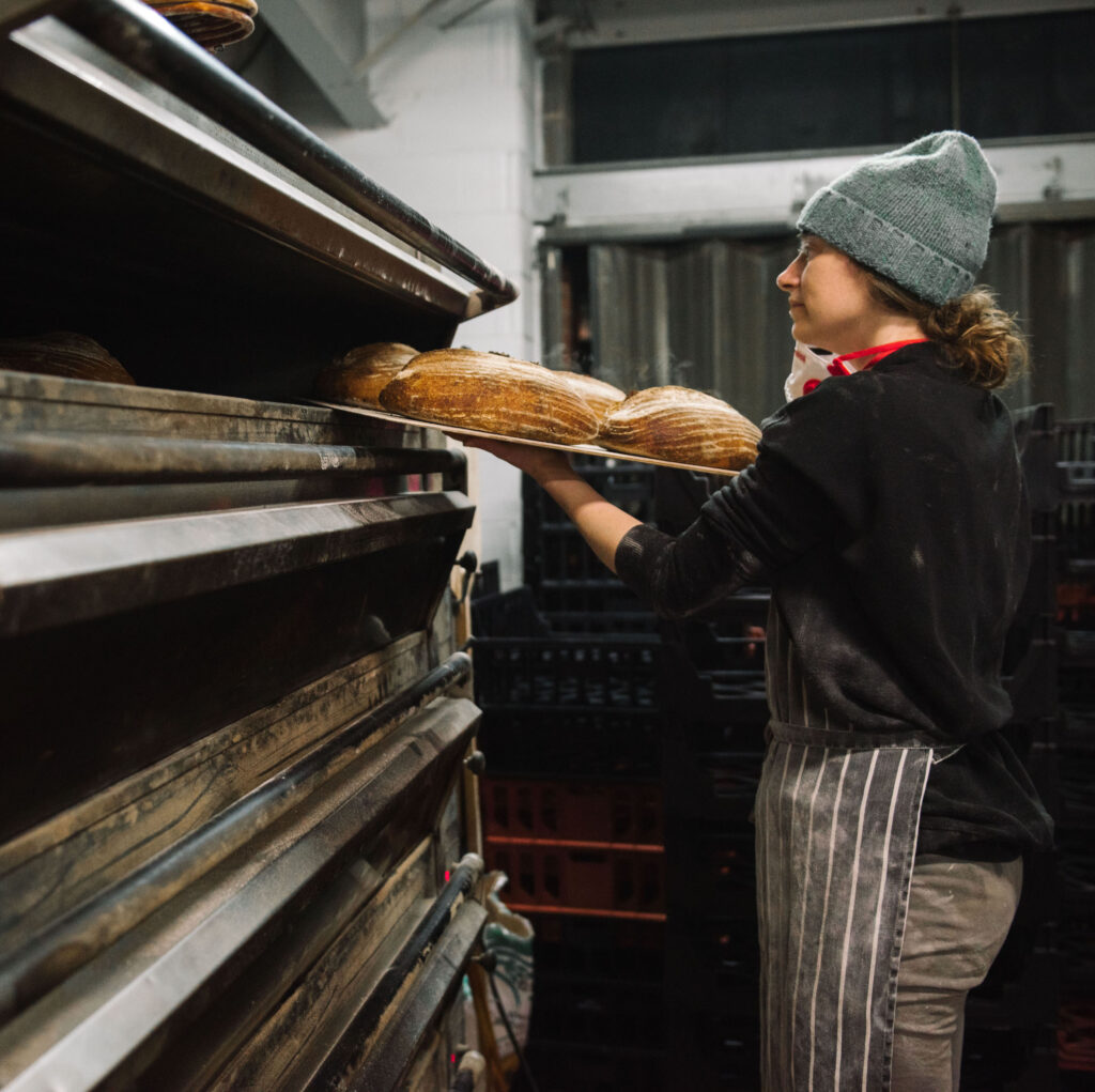 A photo of baker Karen taking some perfectly baked loaves of white sourdough out of the oven.